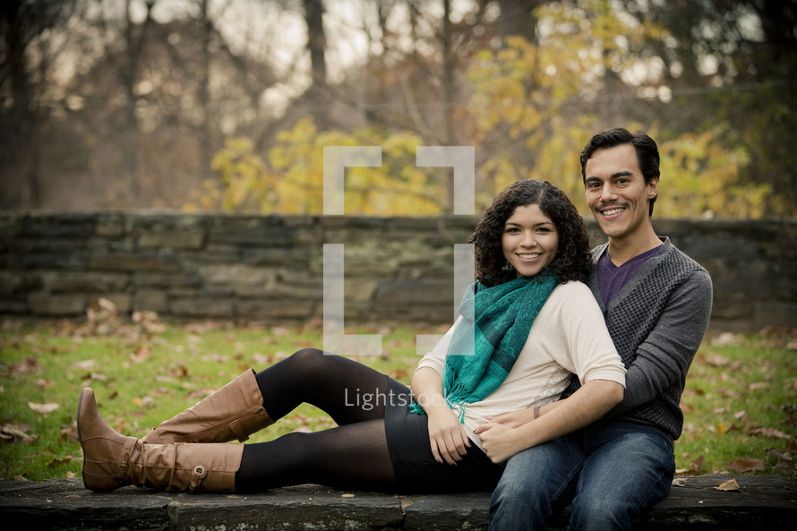woman sitting next to a man with his arms around her