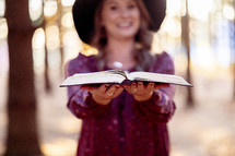 A woman standing in the woods with an open Bible