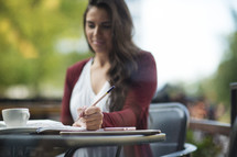 close up of student studying and writing at an outdoor coffee shop.