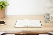 an open Bible and cellphone on a wood desk