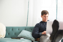 a man on a couch with a laptop