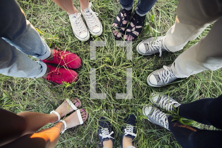 shoes of a diverse group of people in a circle.