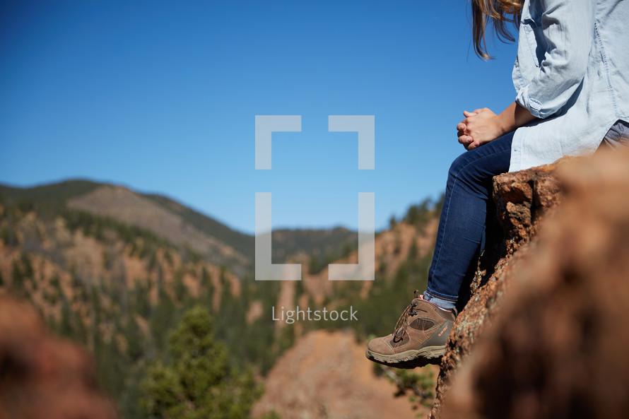 a woman sitting on a rock praying