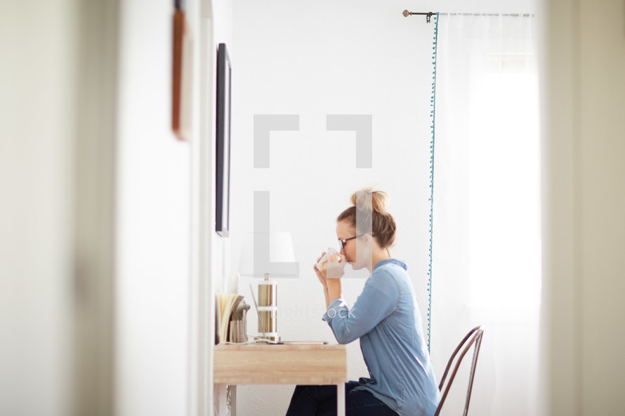 a woman drinking coffee sitting at a desk