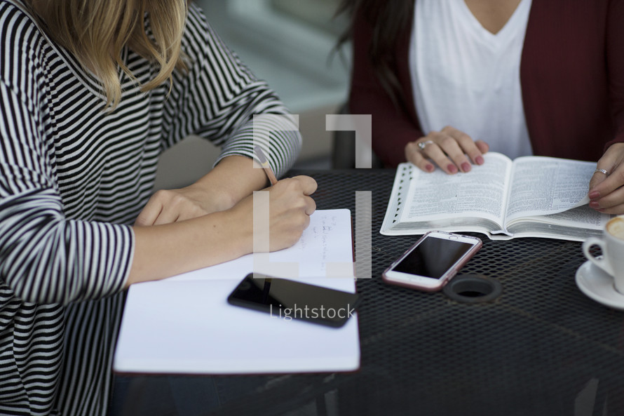 young women reading a Bible and discussing scripture