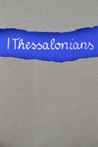 1 Thessalonians - torn open kraft paper over intense blue paper with the name of the first letter from Paul to the Thessalonians