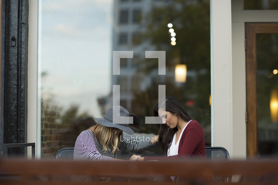 two friends praying together in a city.