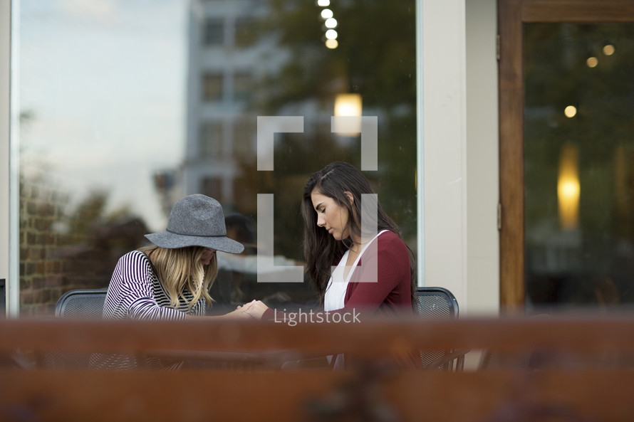 young women reading a Bible and discussing scripture and praying together