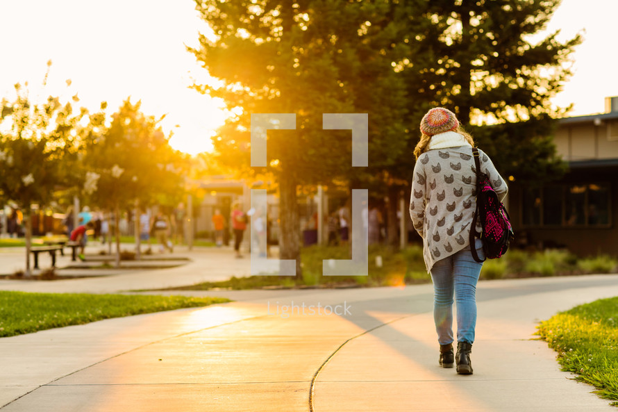 Teenage girl walking back to school, early morning golden sun, backpack, school campus, student, youth