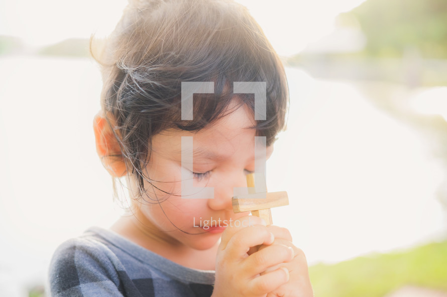 toddler girl holding a wooden cross