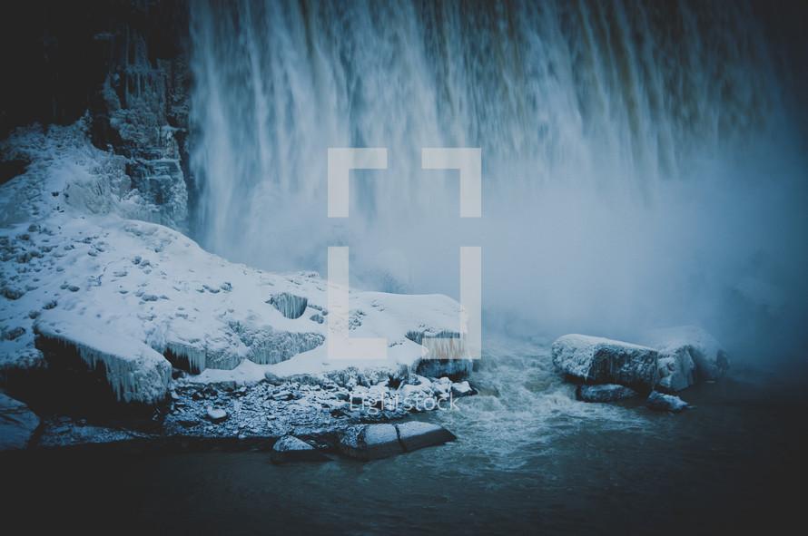 Waterfall onto snow-covered rocks.