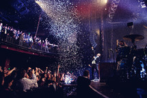 confetti falling on musicians on stage and an audience at a concert