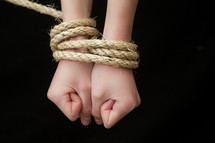 A woman whose wrists are tied.