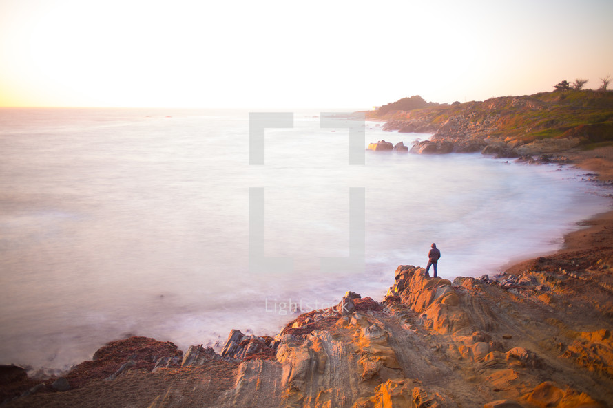distant man standing on a rocky shore