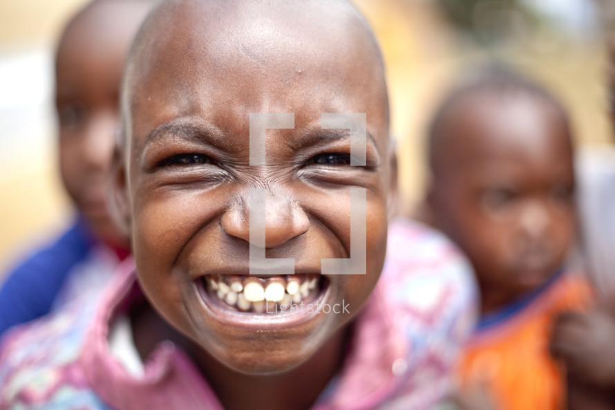 Child in crowd grinning.