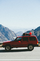 a red SUV parked on the side of the road and view of mountains