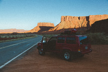 SUV parked on the side of a rock and view of red rock peaks