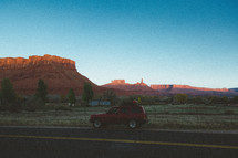 a SUV parked on the side of a road and view of red rock cliffs