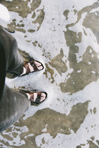a man in sandals standing in shallow ocean water