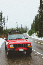 red suv parked on the side of a road and snow