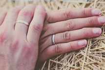 a couple holding hands with wedding bands