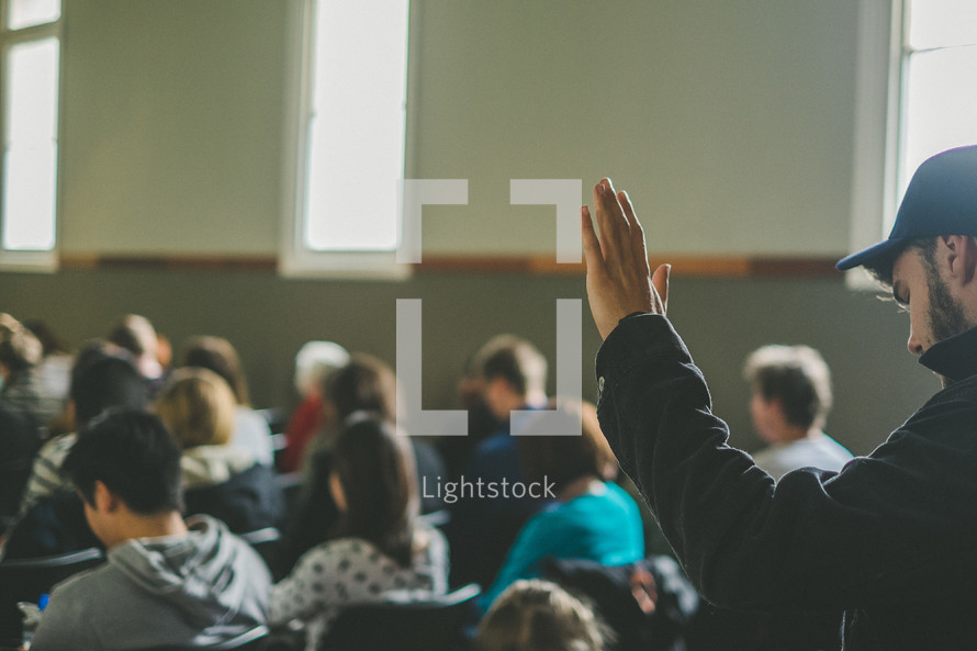 man with a raised hand in class