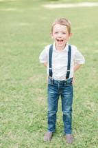 a happy boy child in suspenders