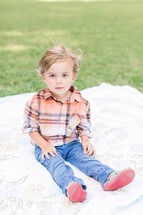a little boy sitting on a blanket in the grass