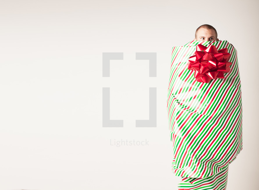A man covered with wrapping paper and bow