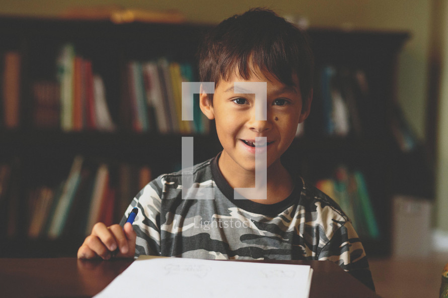 A smiling boy doing his homework