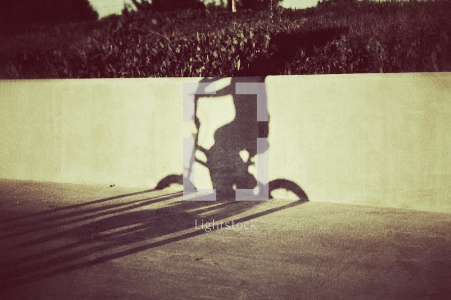 The shadow of a young boy riding his bicycle on the sidewalk