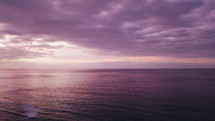 purple clouds over the ocean at sunset
