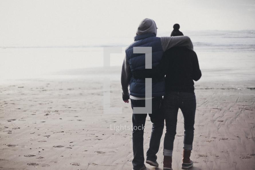 couple walking on a beach in winter coats