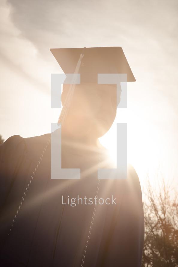 a graduate standing in bright sunlight