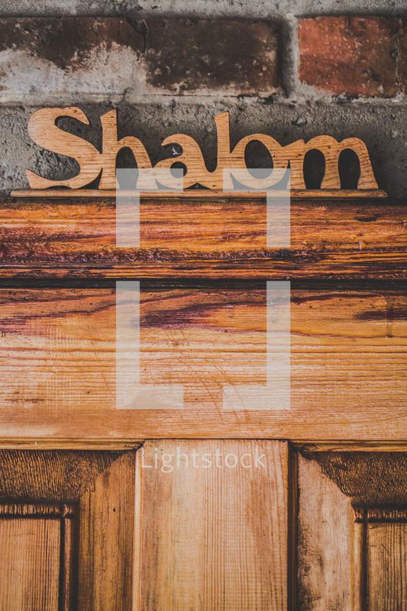 """Wooden """"shalom"""" sign over wooden door."""