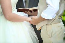 Close up shot of bride and groom holding hands, preacher holding Bible in background.