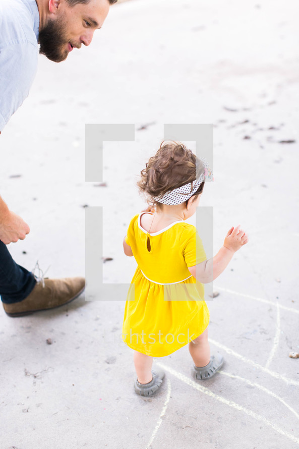 a father watching her toddler daughter walk