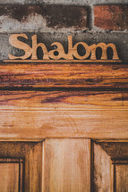 "Wooden ""shalom"" sign over wooden door."