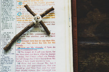"""Rustic handmade cross laying by John 15:13 scripture in Bible that says, """"Greater love has no one than this, that one lay down his life for his friends."""""""