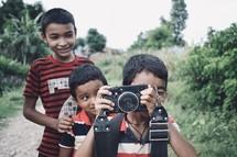 children holding a camera