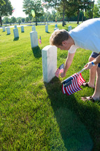 a young man placing American flags near graves