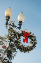 Snow covered Christmas wreath on a streetlight.