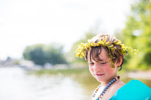 a child in a floatie playing at a lake with a crown of leaves in his hair