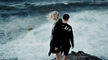 a couple standing on a rocky shore