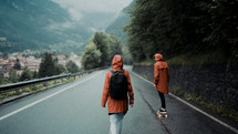 couple in rain gear walking down a rural road