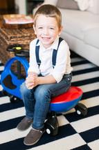 a boy child sitting on a plasma car in a living room