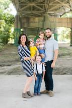 a portrait of a family standing under a bridge