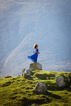 a girl in a dress standing on a rock on a green mountain