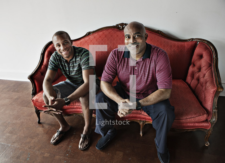two men sitting on couch