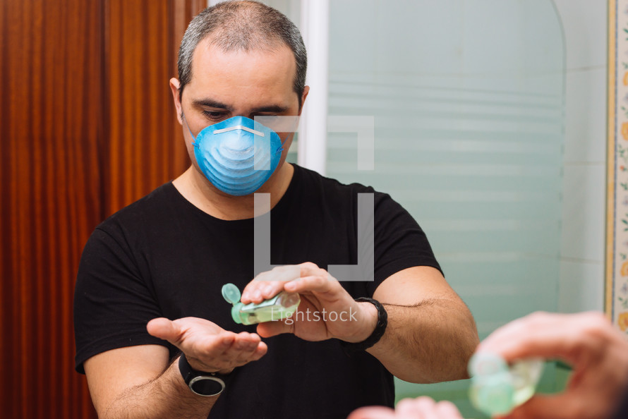 man with face mask applying disinfectant sanitizer onto hand for protection against virus germs